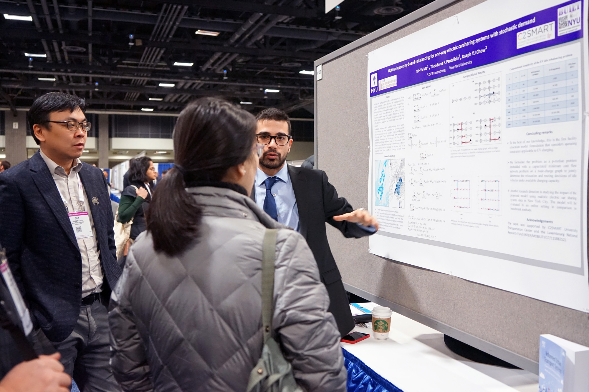 Professor Joseph Chow and graduate student Ted Pantelidis discuss a research poster with conference attendees.