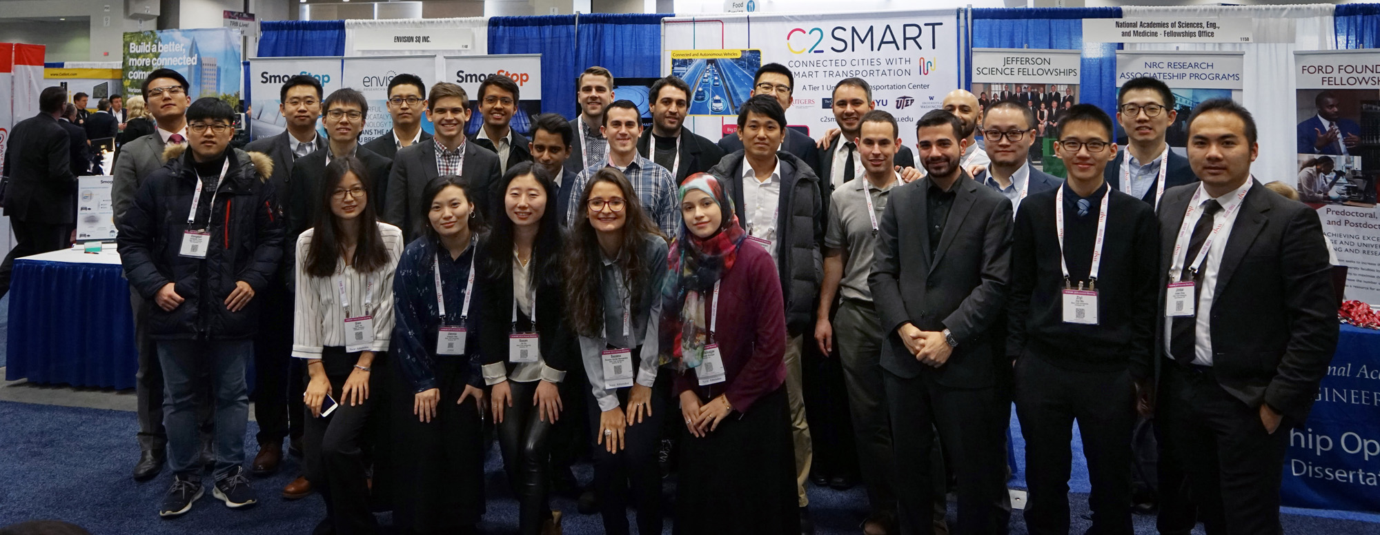 Graduate students attending TRB from Professor Kaan Ozbay's and Joseph Chow's labs pose for a group photo at C2SMART's booth in the Exhibit Hall.
